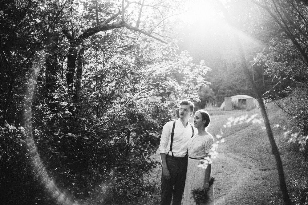 married couple at sunset in rainbow lens flare