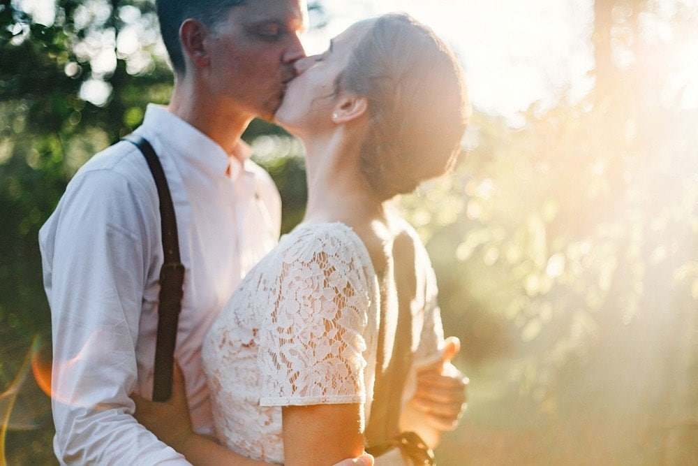 married and kissing at sunset