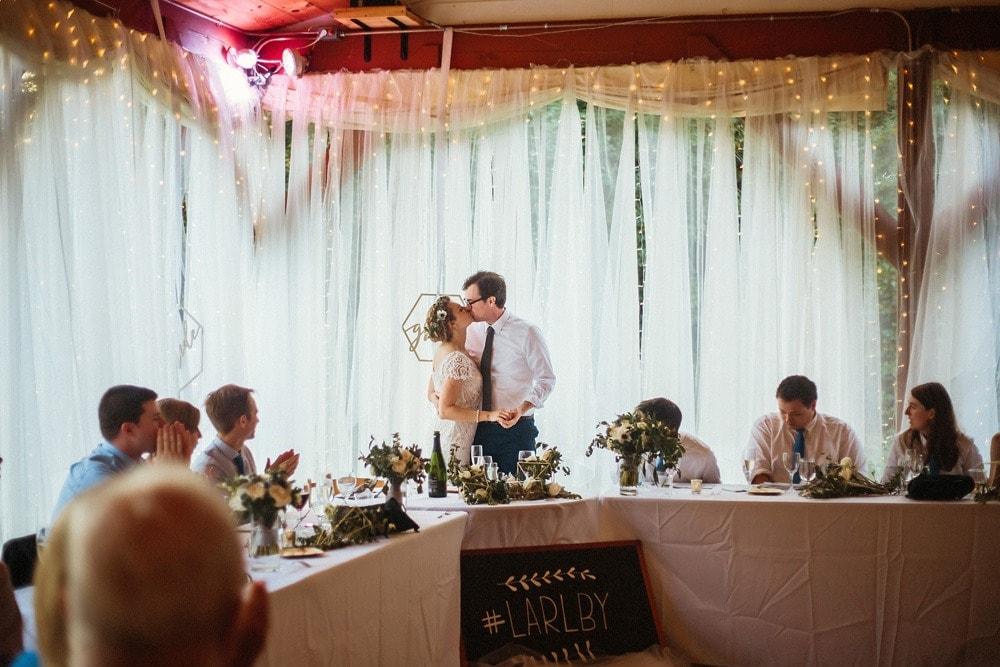 couple kissing during toasts