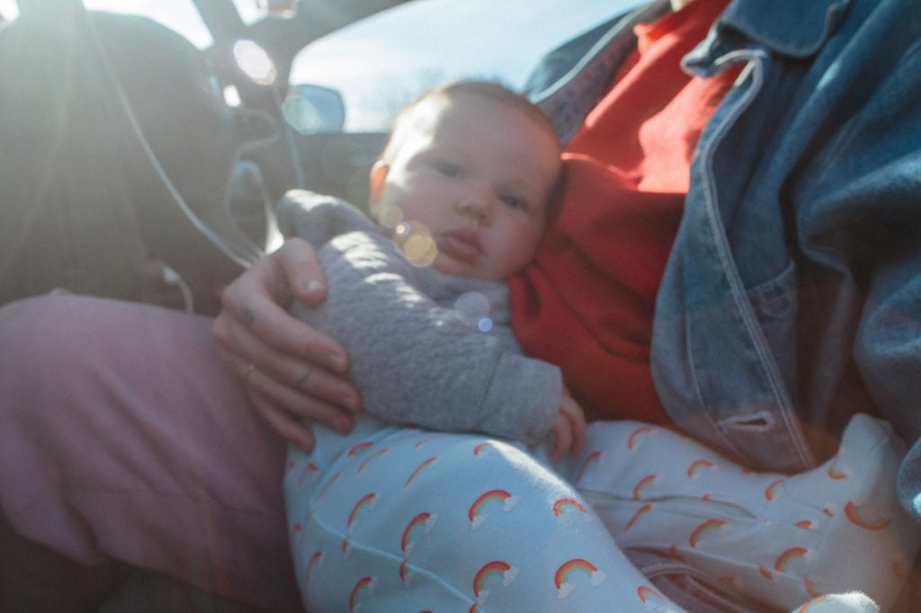 mother and baby front seat of car