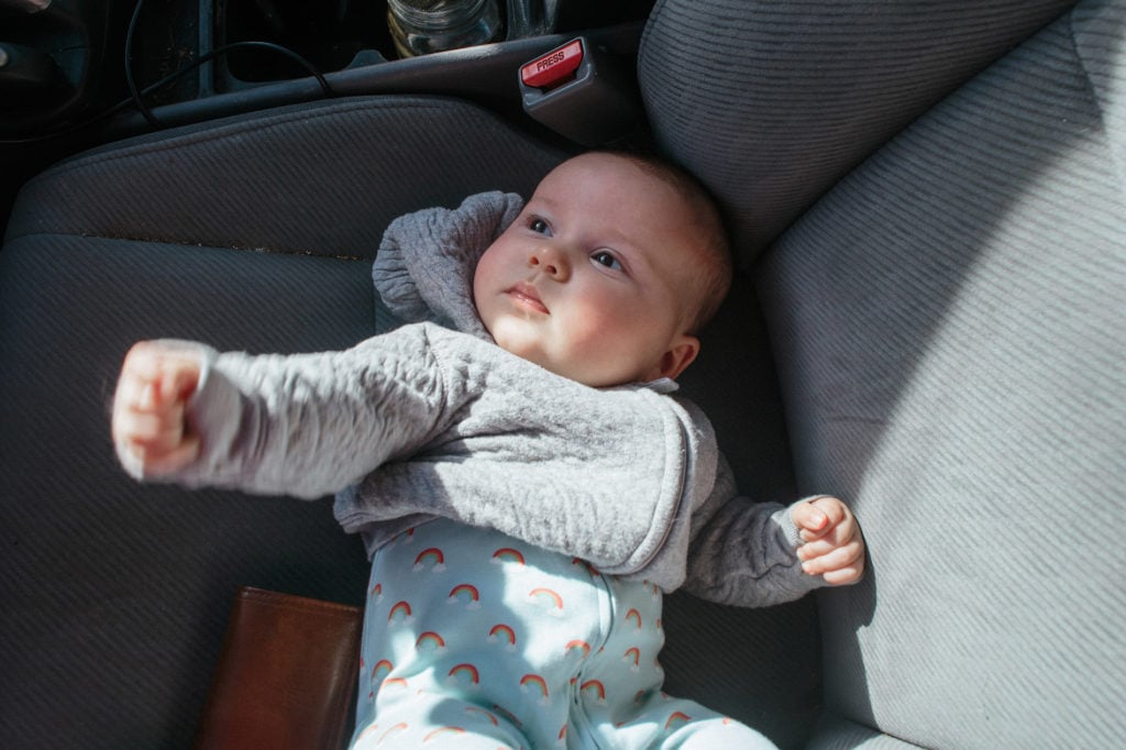 baby lying front seat of car