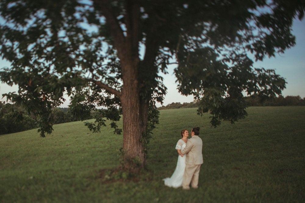 bride and groom embracing under tree