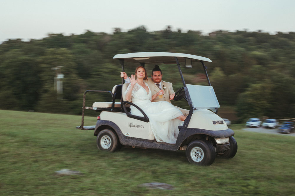 bride and groom riding away in golf cart