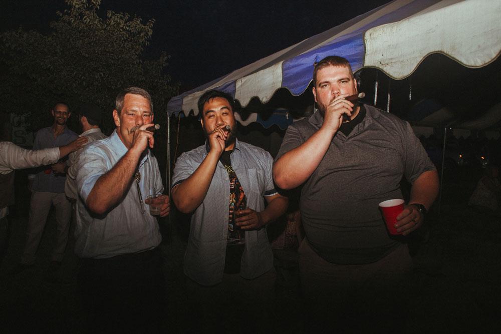 three people smoking cigars at wedding reception